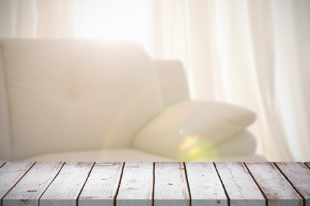 homely: Wooden table against light shining into living room Stock Photo