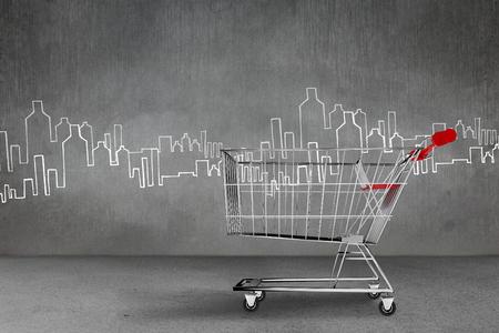urban planning: Shopping cart against hand drawn city plan