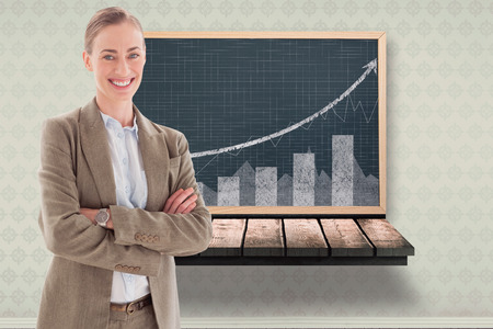 wooden shelf: Smiling businesswoman with crossed arms against black board on a wooden shelf