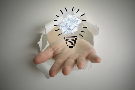 which one: Hand bursting through paper against  five bulbs which one is in the process of function Stock Photo