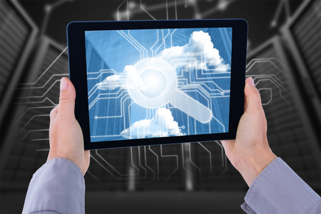 cropped: Cropped hand of man holding digital tablet against a large room where are standing the servers