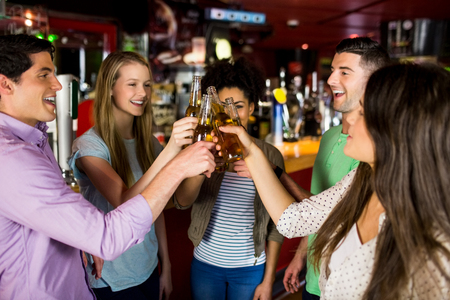 Friends toasting with beer at the bar