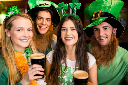Smiling friends with Irish accessory in the bar