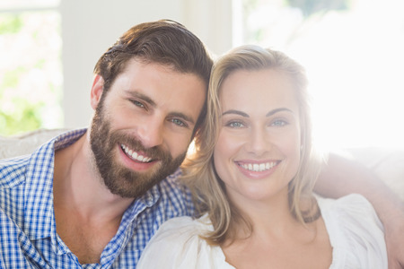arm around: Portrait of smiling couple with arm around at home Stock Photo