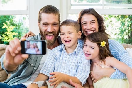 family  room: Smiling family taking selfie in the living room