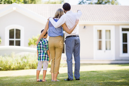 arm around: Rear view of parents and son standing in garden with arm around in front of house