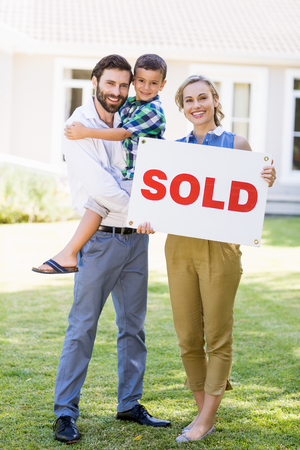 sold sign: Portrait of happy family standing outside home with sold sign Stock Photo