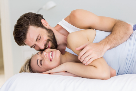 Romantic couple embracing on bed in bedroom Stock Photo
