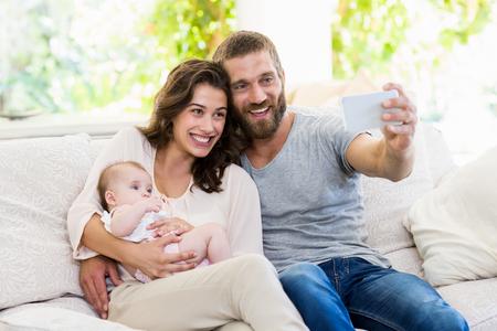 family  room: Family taking selfie on a mobile phone in living room Stock Photo