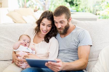 Famille assise sur un canapé à l'aide d'une tablette numérique dans le salon