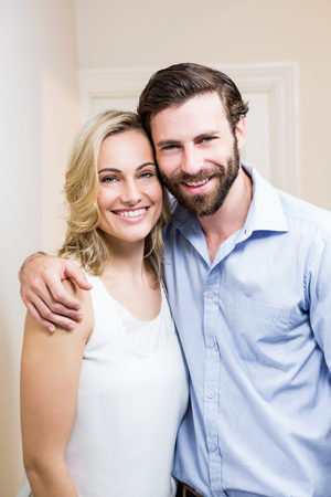 arm around: Happy couple standing with arm around at home Stock Photo