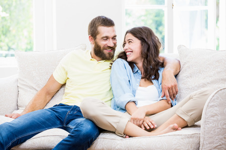 arm around: Young couple sitting on sofa with arm around at home Stock Photo