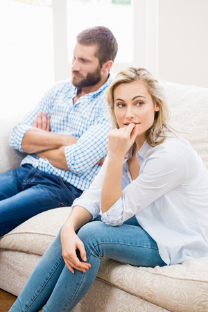 ignoring: Young couple ignoring each other in living room at home