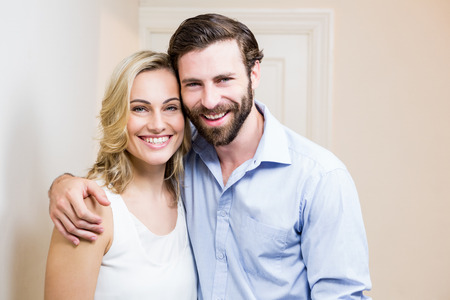 arm around: Portrait of happy couple standing with arm around at home Stock Photo