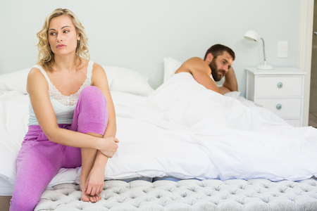 ignoring: Upset couple ignoring each other after fight on bed in bedroom
