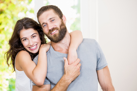 embracing couple: Portrait of young couple embracing at home Stock Photo