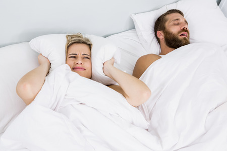 snoring: Woman covering ears while man snoring on bed at home