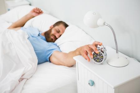awakened: Sleeping man awakened by a alarm on bed at bedroom