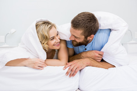 other: Happy couple looking at each other on bed in bedroom Stock Photo