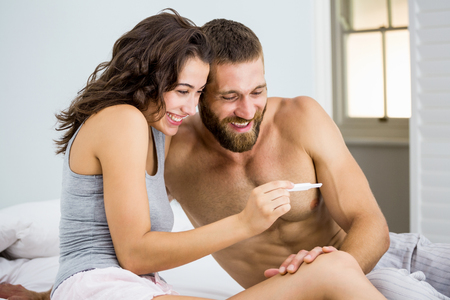 prueba de embarazo: feliz pareja mirando la prueba de embarazo en cama en el dormitorio Foto de archivo