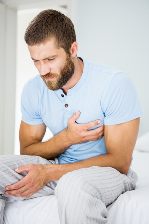chest pain: Young man having chest pain in bed at bedroom