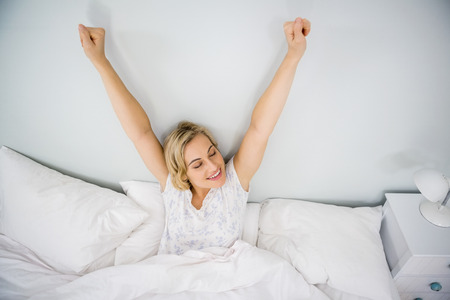 rested: Woman stretching her arms in bed in bedroom