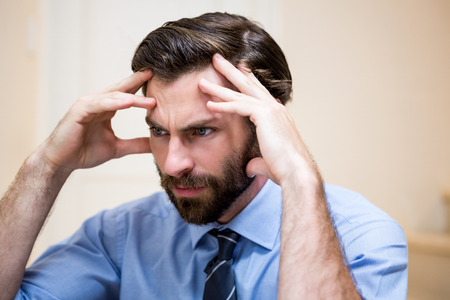 tensed: Close up of tensed man with hands on forehead at home Stock Photo