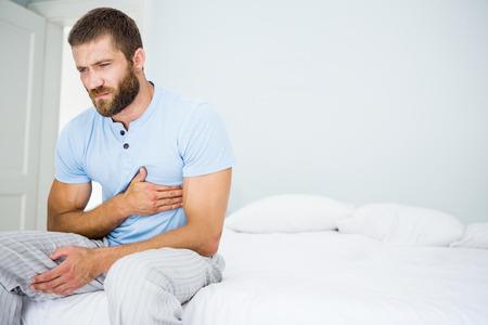 dolor de pecho: Hombre joven que tiene dolor en el pecho en la cama en el dormitorio
