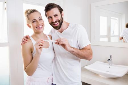 prueba de embarazo: Portrait of happy couple checking pregnancy test in bathroom