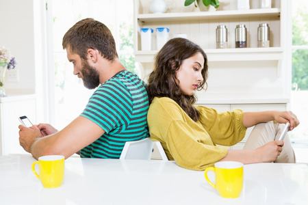 messing: Couple sitting back to back and text messing on mobile phone at home Stock Photo