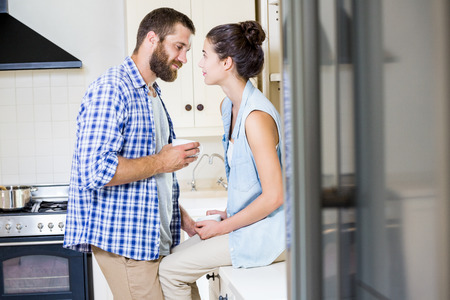 each other: Happy young couple looking each other in kitchen at home Stock Photo