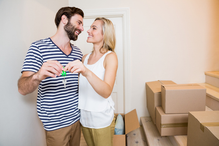 Happy couple holding keys in their new house