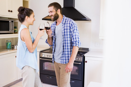toasting wine: Young couple toasting wine glass in kitchen at home
