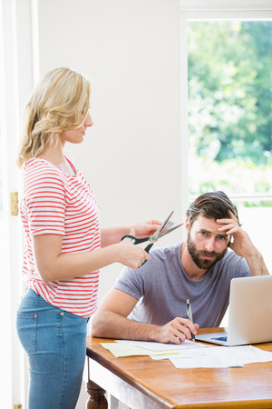 tense: Woman cutting a credit card while tense man with bills sitting at table at home