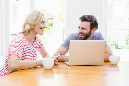 each other: Couple looking at each other while using laptop at home Stock Photo