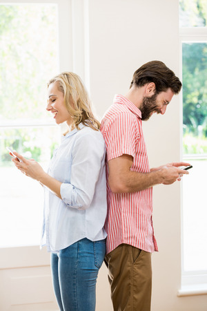 messing: Couple standing back to back and text messing on mobile phone at home Stock Photo