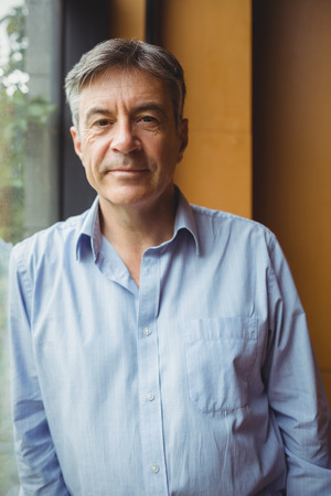 Portrait de professeur debout près d'une fenêtre à l'université