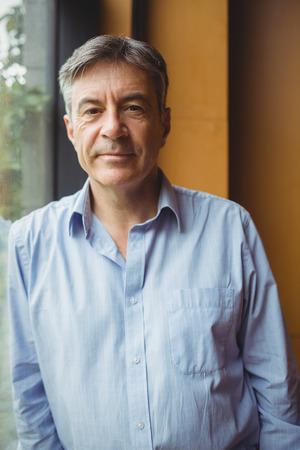 Retrato del profesor de pie cerca de una ventana en la universidad