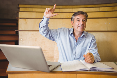 adult hand: Confident professor raising his hand in classroom at college