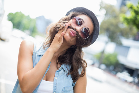 pulling faces: Young woman in sunglasses pulling funny faces Stock Photo