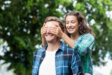 covering: Happy woman covering her mans eyes Stock Photo