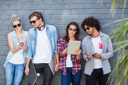 mobile internet: Friends in sunglasses leaning against wall using mobile phone and digital tablet Stock Photo