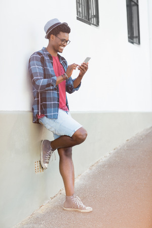leaning against: Happy young man leaning against wall using mobile phone