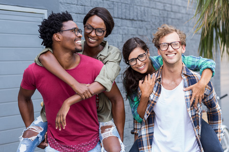 couples outdoors: Happy young men giving piggyback to women Stock Photo