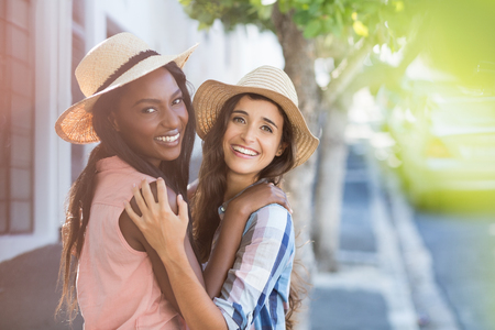 Portrait of friends in hat embracing each other Stock Photo