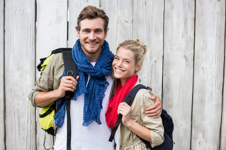 Portrait of happy young couple carrying backpack