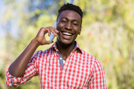 phoning: Happy man using his smartphone at the park Stock Photo