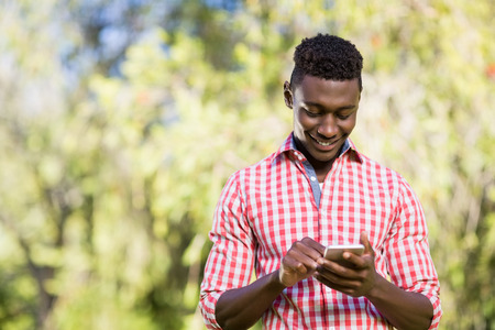 text messaging: Happy man using his smartphone at the park Stock Photo