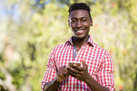 frizzy: Happy man posing and holding his smartphone at park Stock Photo