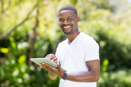 using tablet: Happy man using a tablet at park